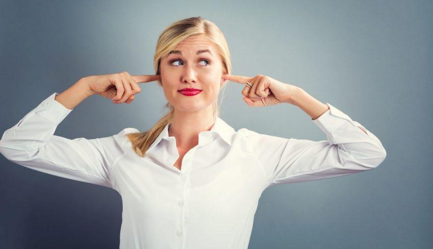 zatkane uszy - kobieta zatyka uszy palcami