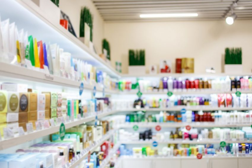 Dwie sklepowe półki, na każdej z nich roi się od kosmetyków róznego rodzaju