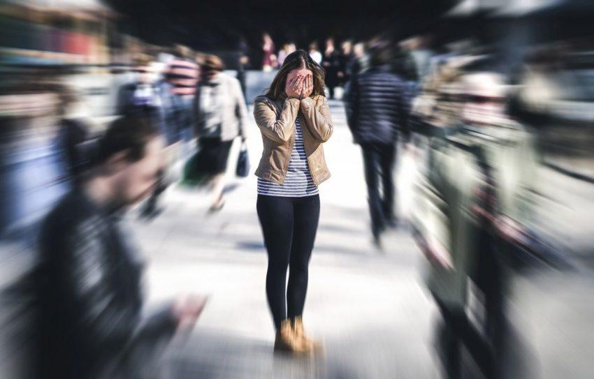 Kobieta wśród ludzi mająca objawy schizofrenii prostej