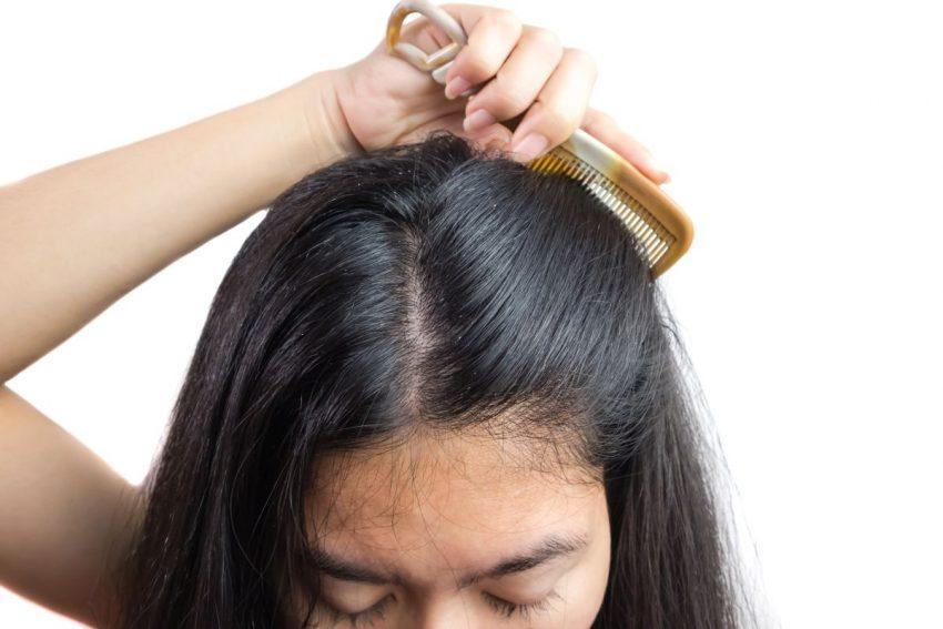przetłuszczające się włosy - kobieta czesząca włosy