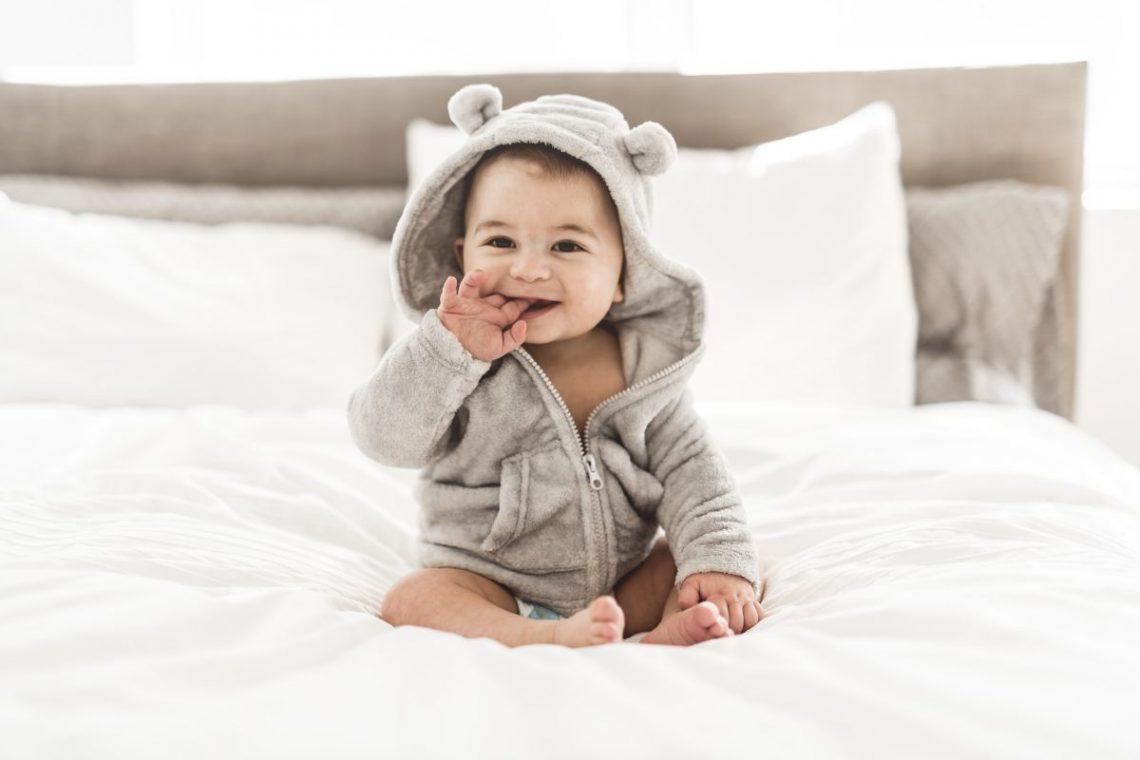 Małe dziecko w kombinezonie siedzi na łóżku i patrzy przed siebie