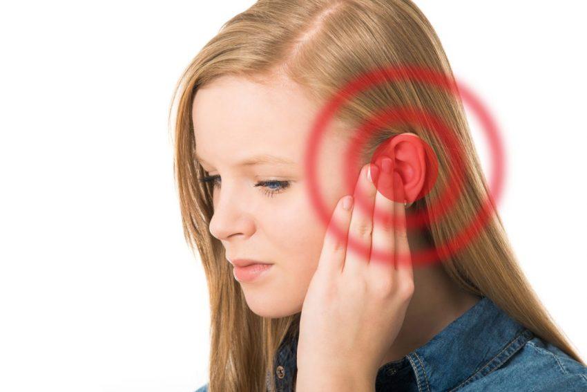 szum w uszach - kobieta trzyma się za ucho