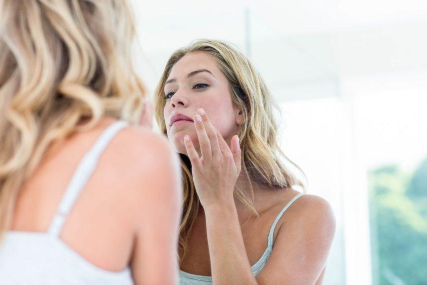 teleangiektazje - kobieta przeglądająca się w lustrze