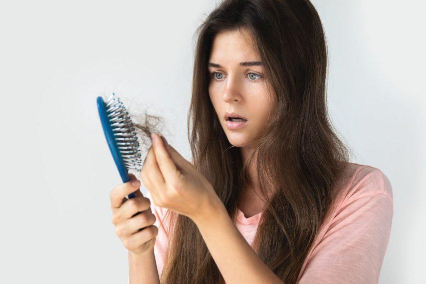 Kobieta wyjmująca wypadające włosy ze szczotki