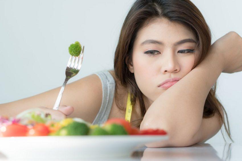 zaburzenia odżywiania - kobieta nad talerzem z warzywami