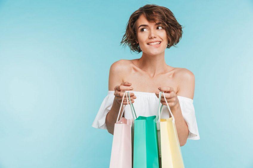 Kobieta stoi z kolorowymi torbami na zakupy
