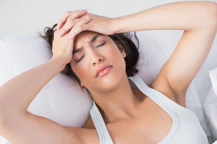 zatrucie alkoholowe - kobieta leży w łóżku i trzyma się za głowę