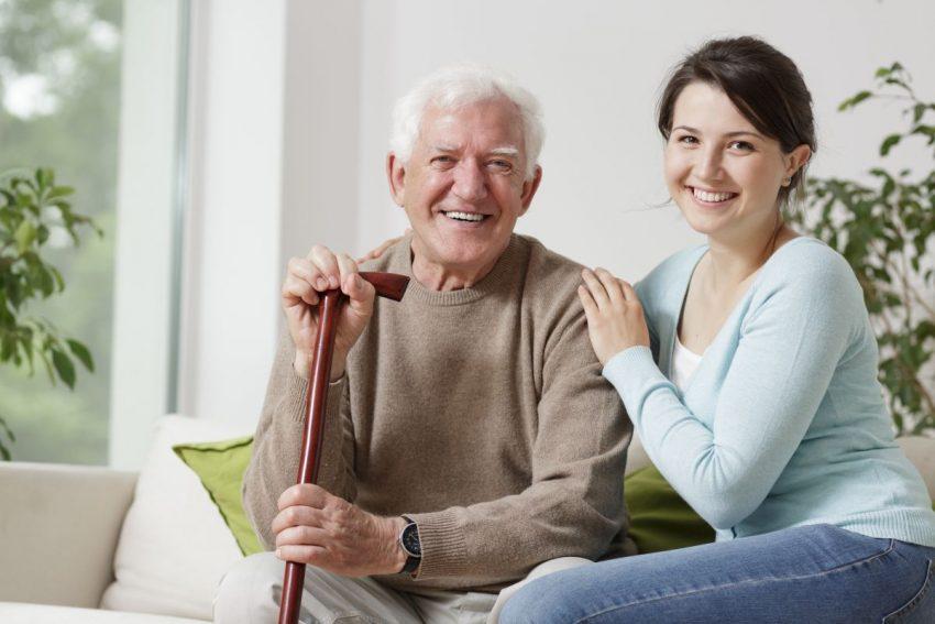 Stary człowiek siedzi z laską, obok niego siedzi młoda kobieta w niebieskiej bluzce, która się uśmiecha do obiektywu.