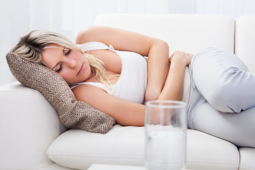 Kobieta cierpiąca na achalazję leży skulona i trzyma się za brzuch.