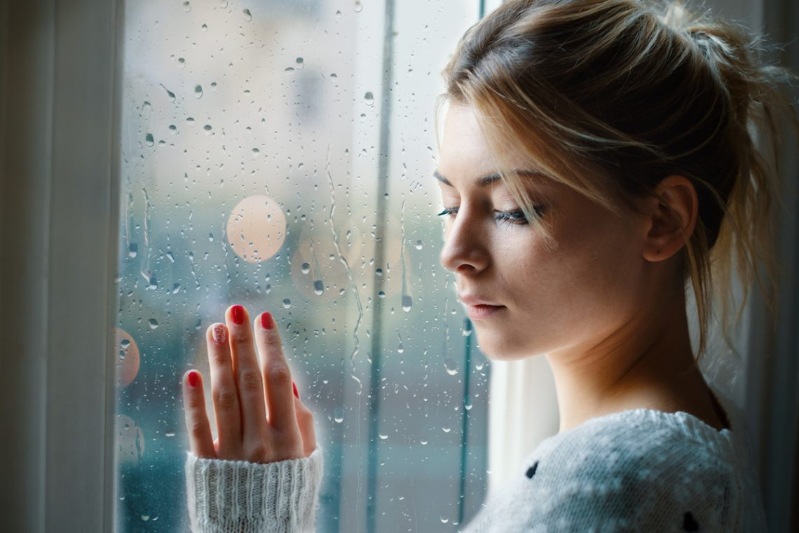 Młoda kobieta zarażona AIDS ze smutkiem spogląda przez okno.