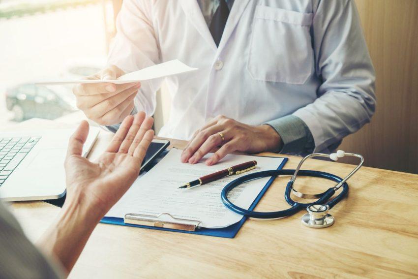 Lekarz wręcza pacjentce potwierdzenie badań lekarskich