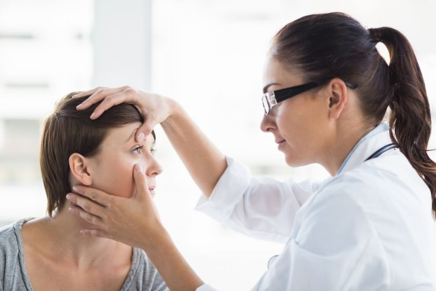 Lekarka w okularach robi badanie okulistyczne pacjentce w krótkich włosach