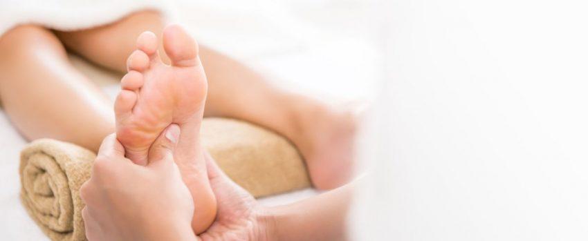 Fizjoterapeuta wykonuje kobiecie masaż śródstopia