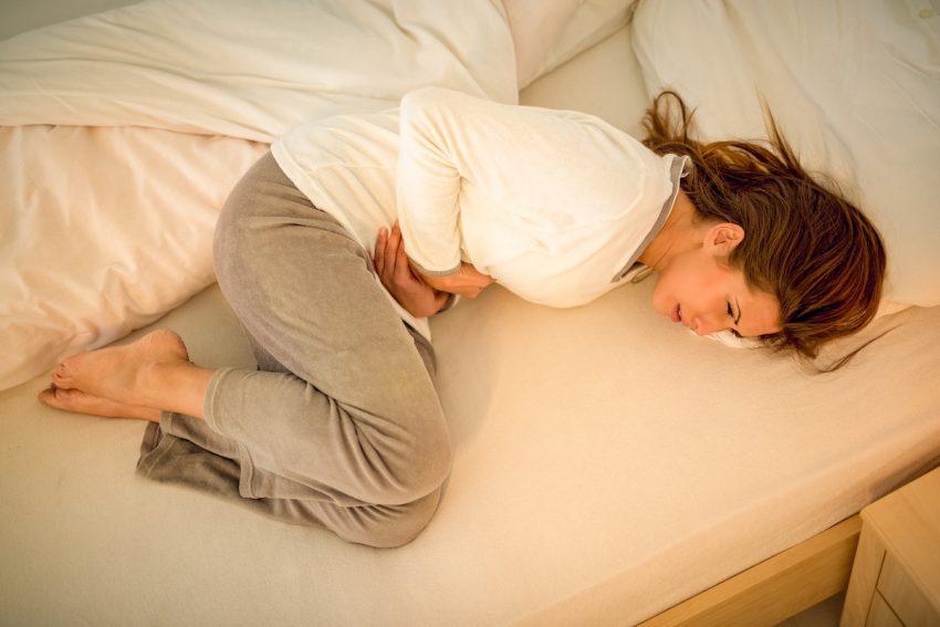Kobieta z chorobą Addisona leży skulona na łóżku i trzyma się za brzuch.