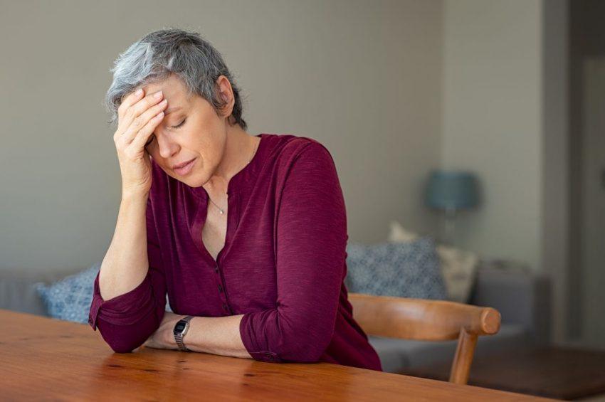 Kobieta siedzi przy stole i trzyma się za głowę