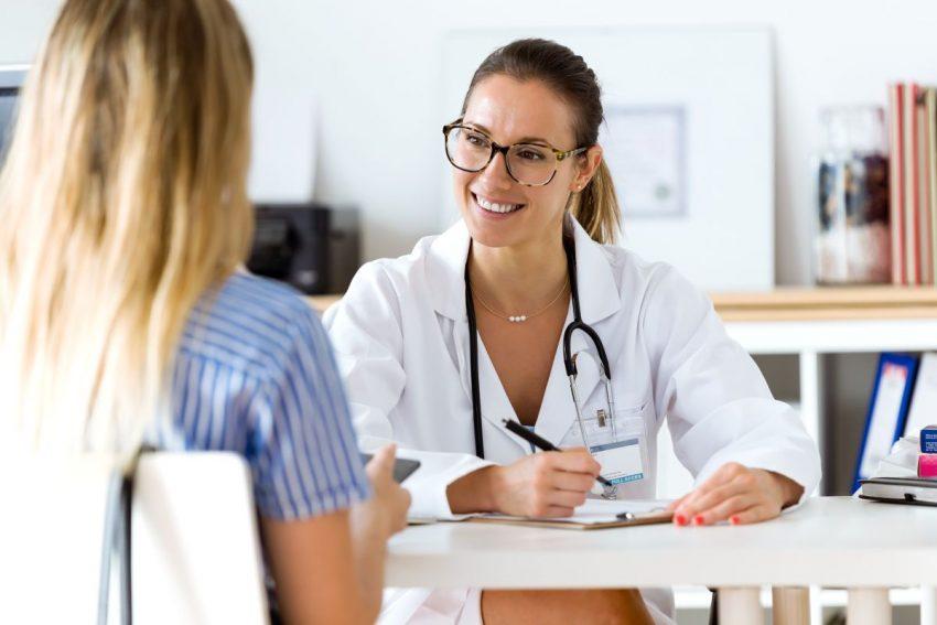 Lekarka w okularach przepisuje receptę pacjentce