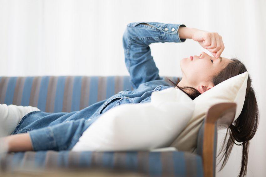 Młoda kobieta cierpiąca na czerwienicę leży z zamkniętymi oczami.