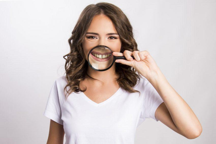 kobieta trzymająca lupę, na wysokości ust
