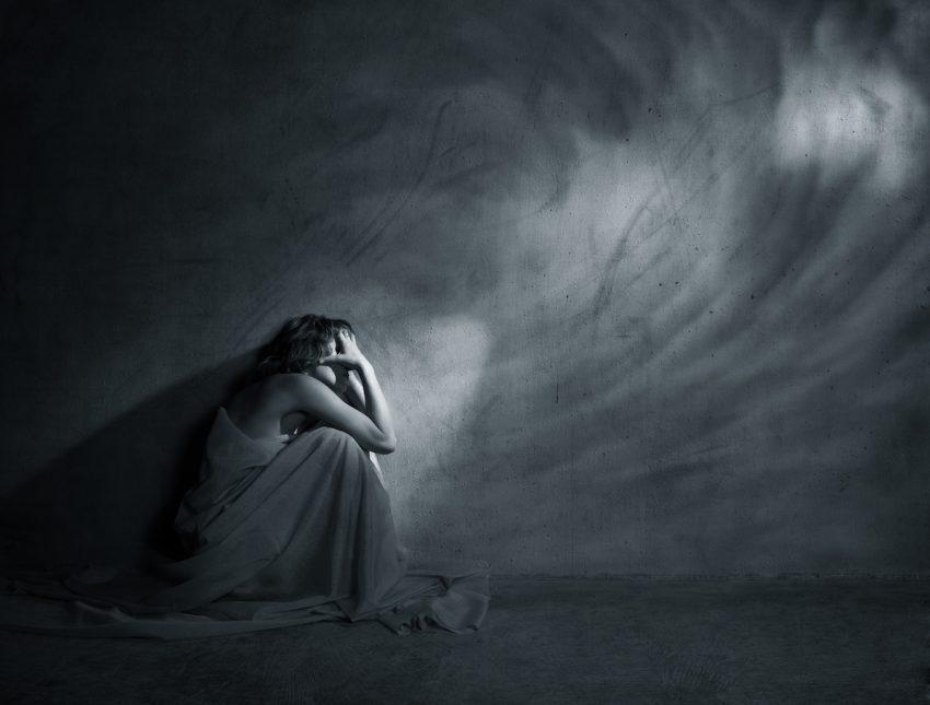 Kobieta cierpiąca na derealizację siedzi skulona na ziemi.