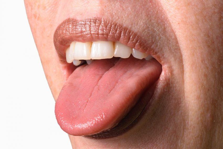 Kobieta wystawia zza zębów jezyk