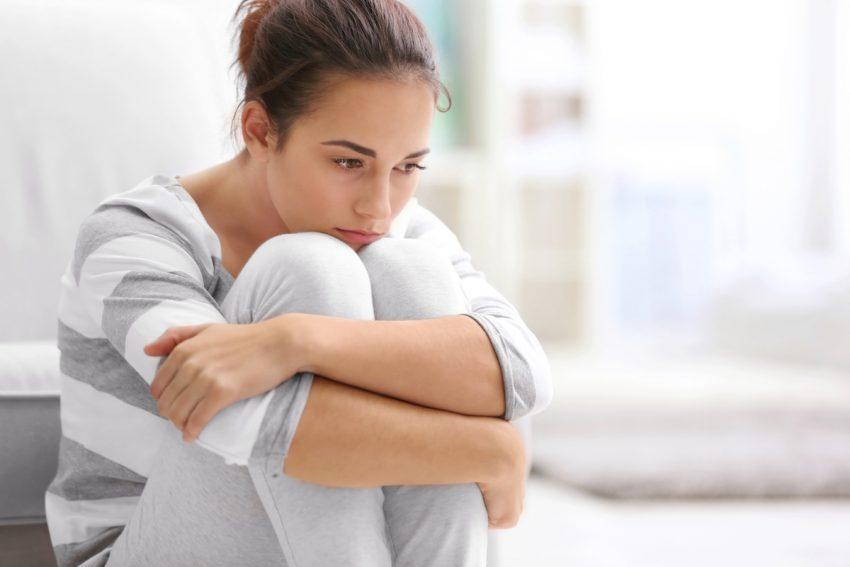 Kobieta cierpiąca na dystymię siedzi smutna na podłodze obejmując kolana rękami.