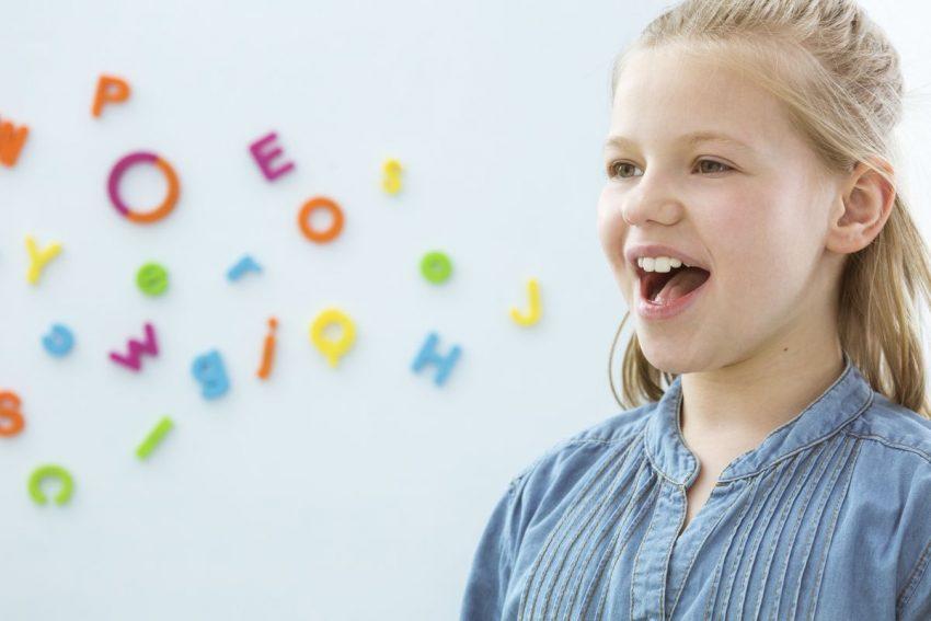 Po lewej stronie dziewczynka, a po prawej stronie kolorowe literki