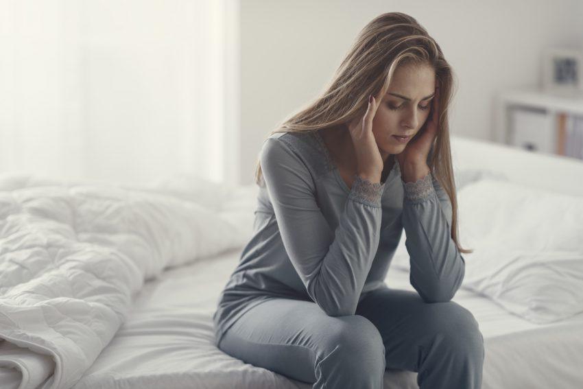 Kobieta cierpiąca na epilepsję siedzi na łóżku z przymkniętymi oczami.