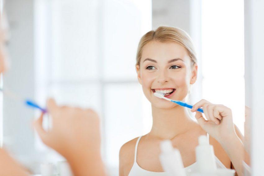 młoda kobieta w łazience myje zęby szczoteczką