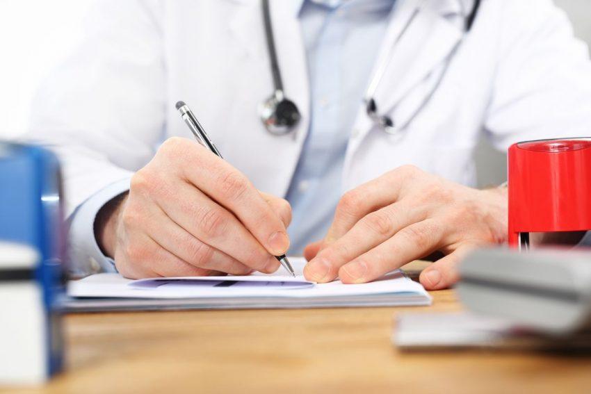 Lekarz siedzi przy biurku i wypisuje długopisem skierowania