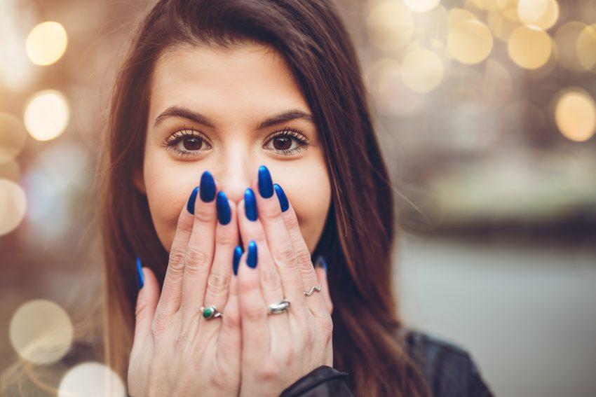 młoda kobieta zakrywa usta dłońmi