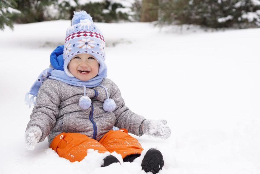 dziecko w ciepłym ubraniu siedzi na śniegu
