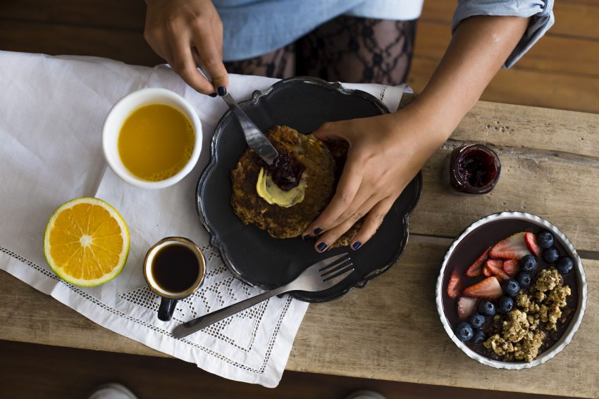 kobieta smaruje naleśnika masłem obok stoi miska z granolą,kubek z kawą oraz połówka pomarańczy