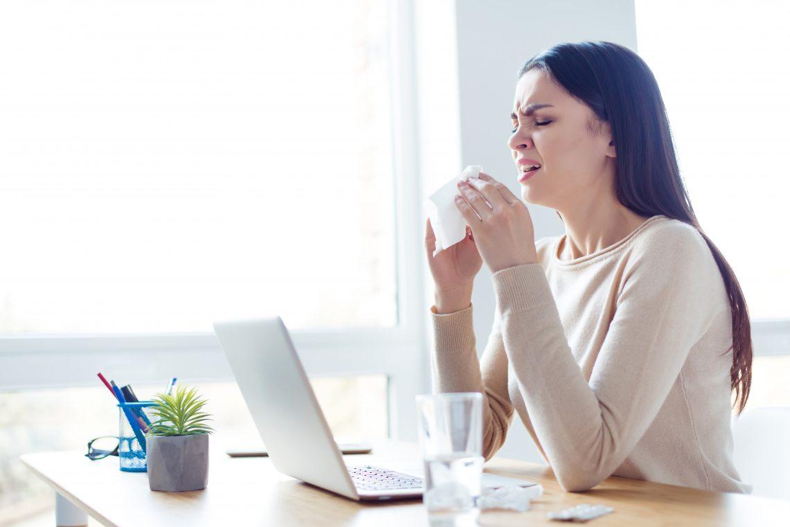 kichająca kobieta w pracy