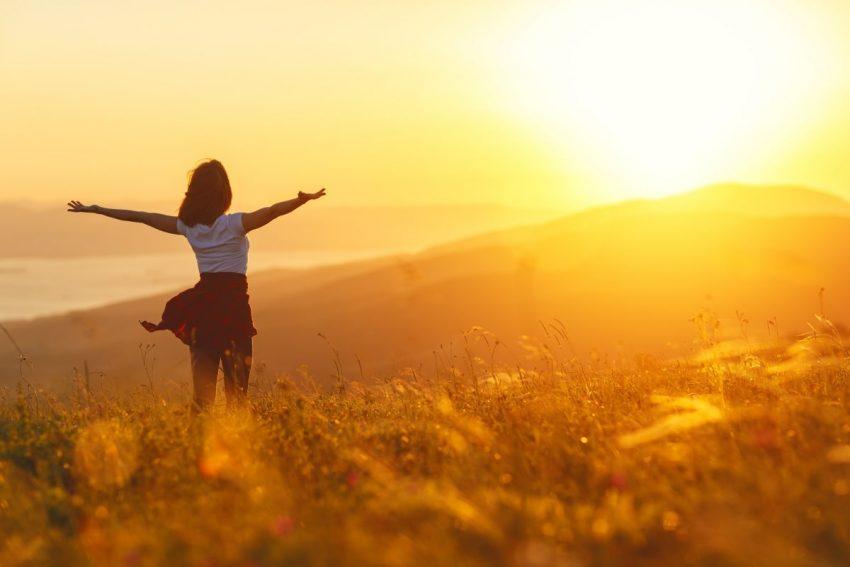 kobieta stojąca na przeciwko słońca