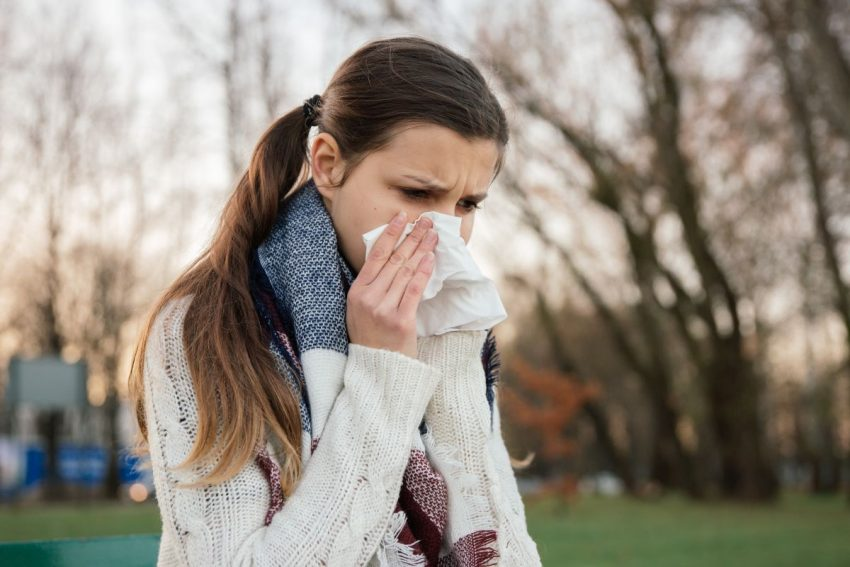 Kobieta chodzi po parku i trzyma chusteczkę przy nosie