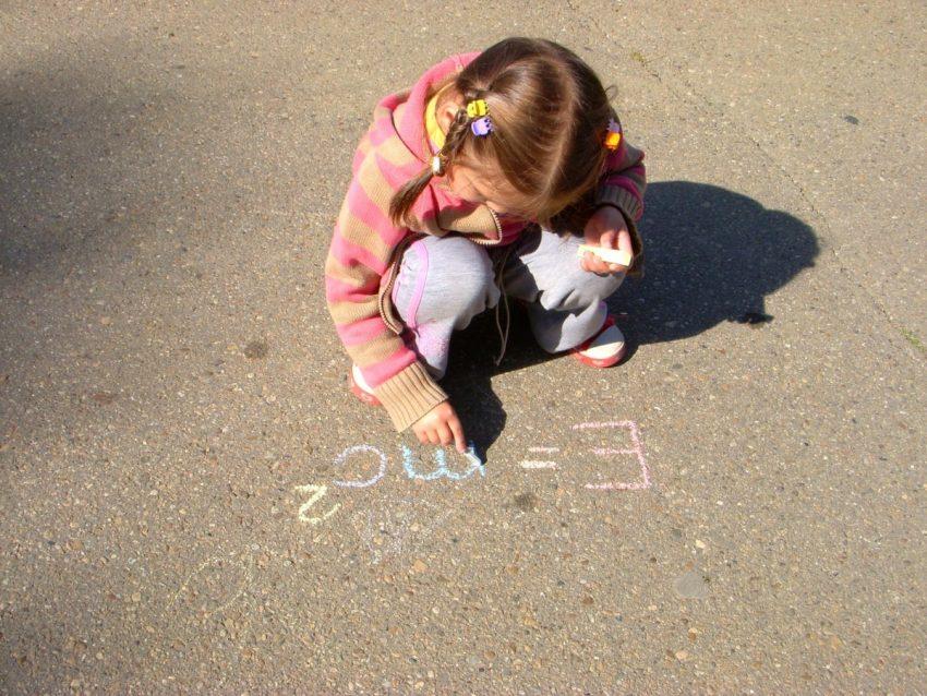 dziewczyna malująca kredą po asfalcie