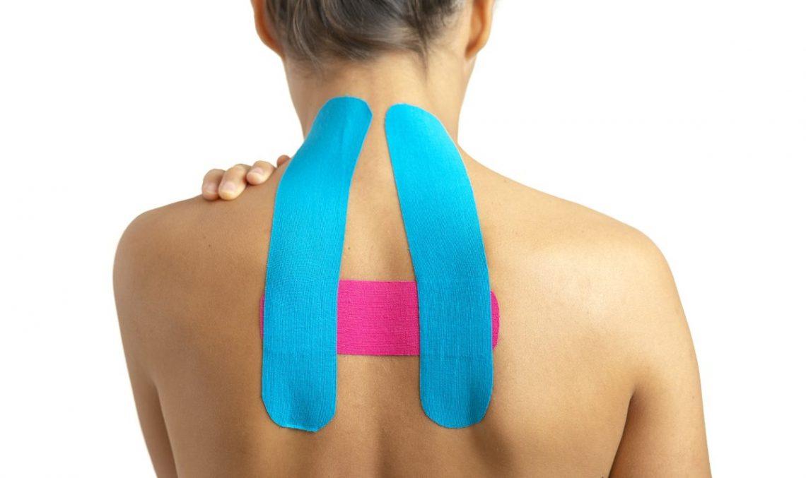 kobieta odwrócona plecami ma naklejone kolorowe plastry na górze pleców