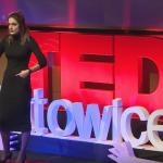 młoda kobieta w czarnych ciuchach stoi na scenie podczas konferencji tedx