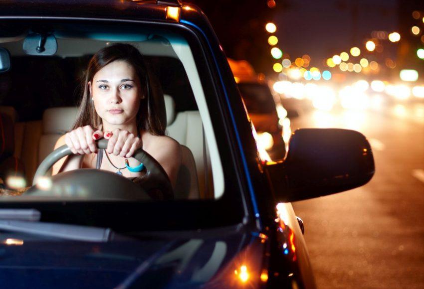 Kobieta jedzie samochodem w nocy