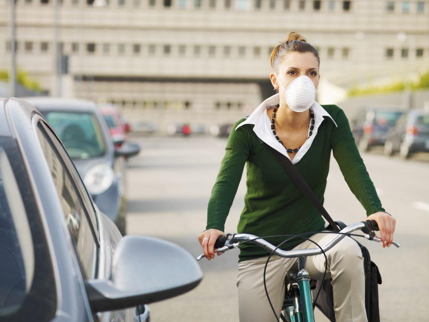 Kobieta jadąca na rowerze w masce antysmogowej