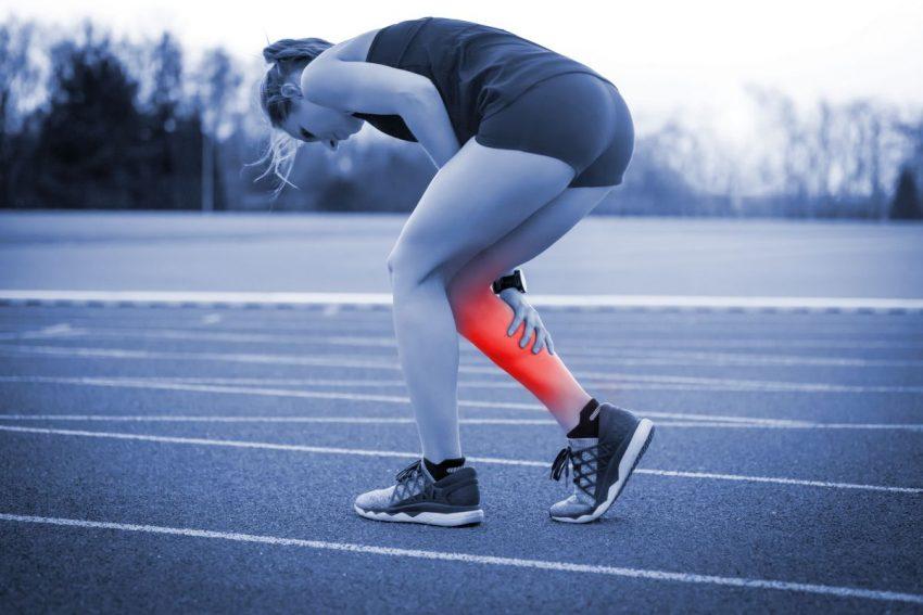 kobieta biegająca na bieżni trzyma się za bolącą łydkę