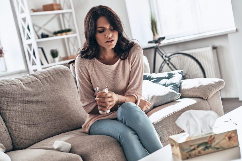 Kobieta cierpiąca na nadkwasotę siedzi zgarbiona na kanapie.