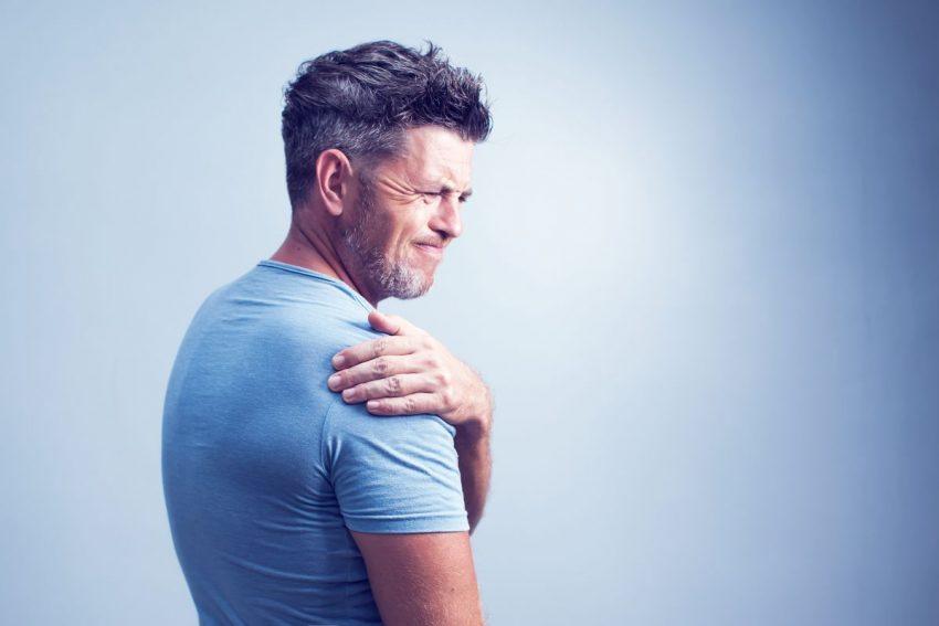 Mężczyzna w niebieskiej koszulce trzyma się za ramię