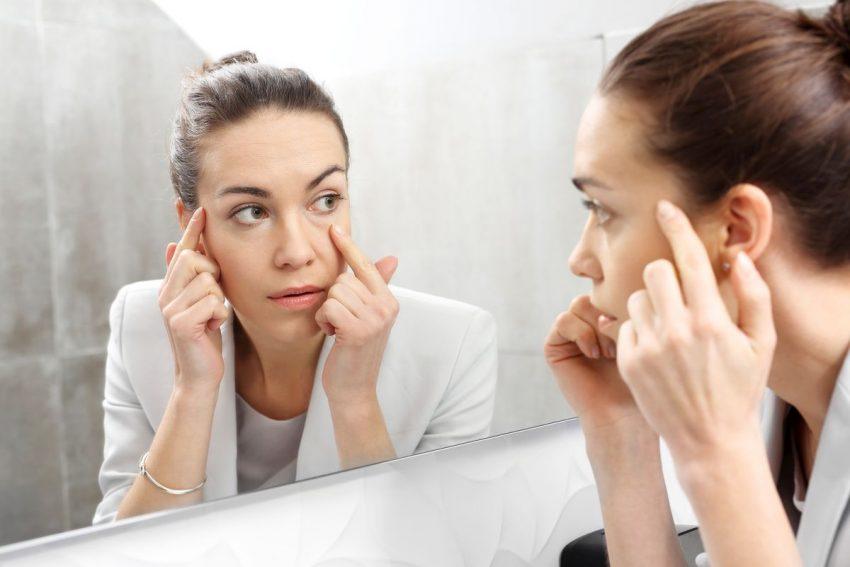 Kobieta stoi przed lustrem i trzyma się jedną ręką za skroń, a drugą pod okiem