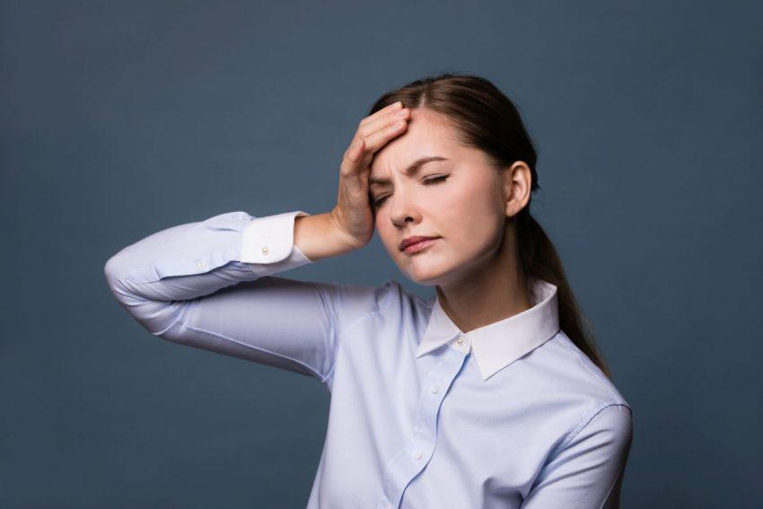 zmęczona młoda kobieta trzyma się za czoło