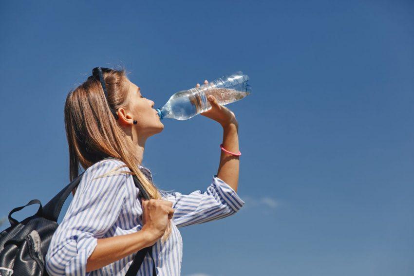 odwodnienie organizmu - kobieta pije wodę z butelki