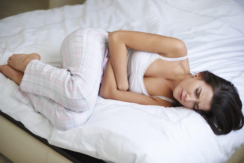 Kobieta z chorą trzustką leży skulona na łóżku i trzyma się za bolący brzuch.