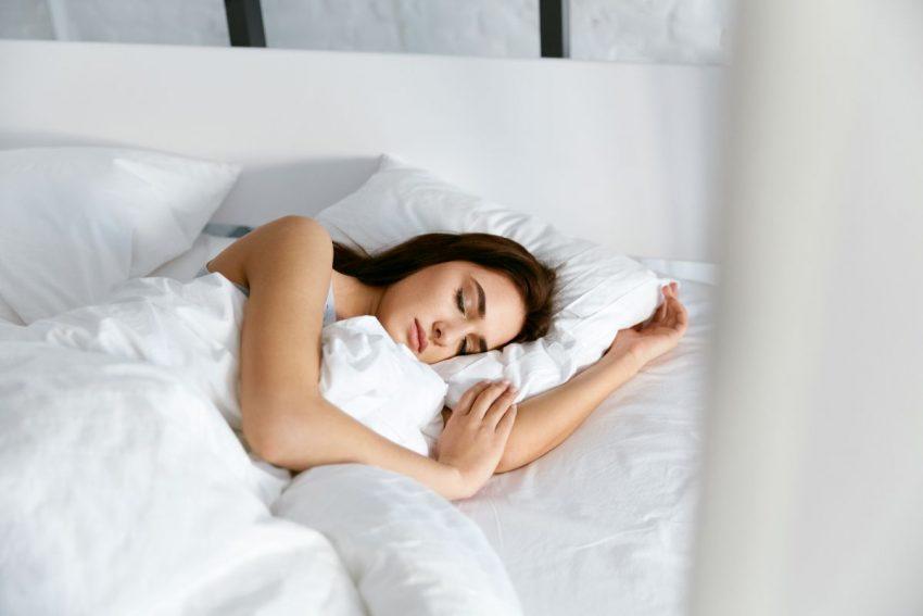 Kobieta w ciemnych włosach śpi w białej pościeli