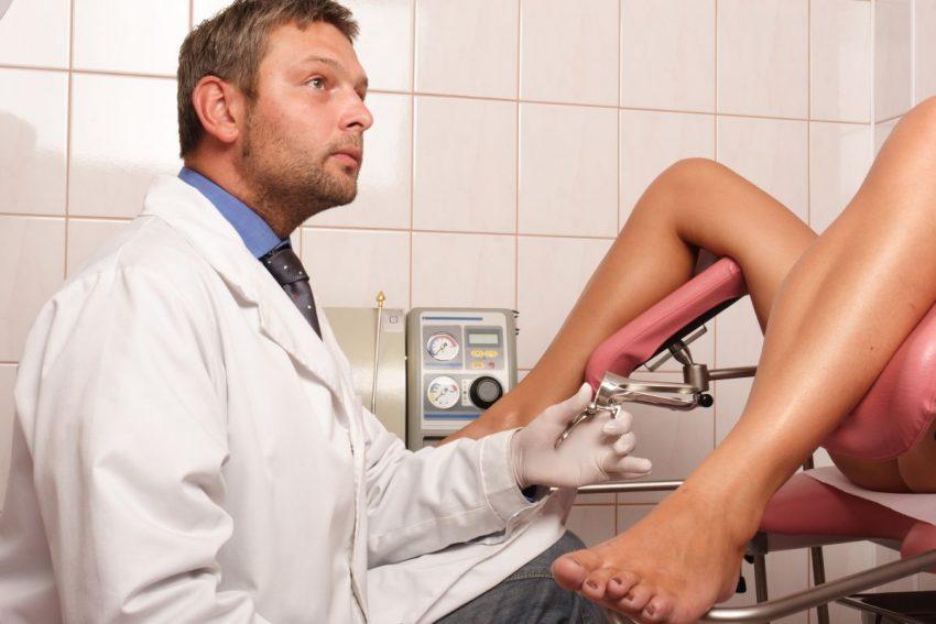 Lekarz w białym kitlu wykonuje badanie ginekologiczne.
