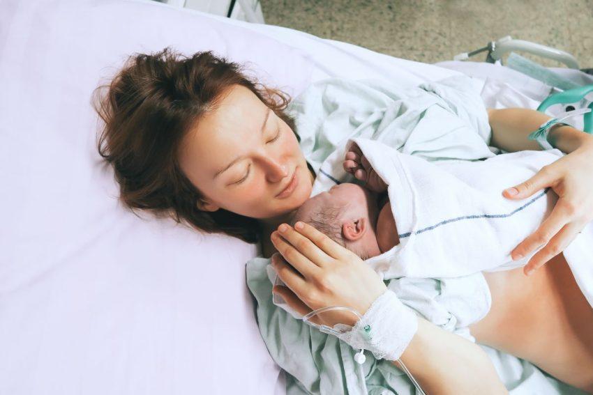 Kobieta po porodzie trzyma noworodka na piersiach